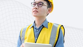 Construction worker with yellow vest on a tablet